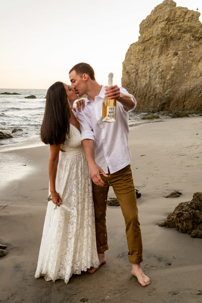 """A man and woman in white on the rocky beach in California. They're kissing and holding a bottle of Rose bubbly that says """"Yes Way Rose"""" Photo by Gabby Jockers."""