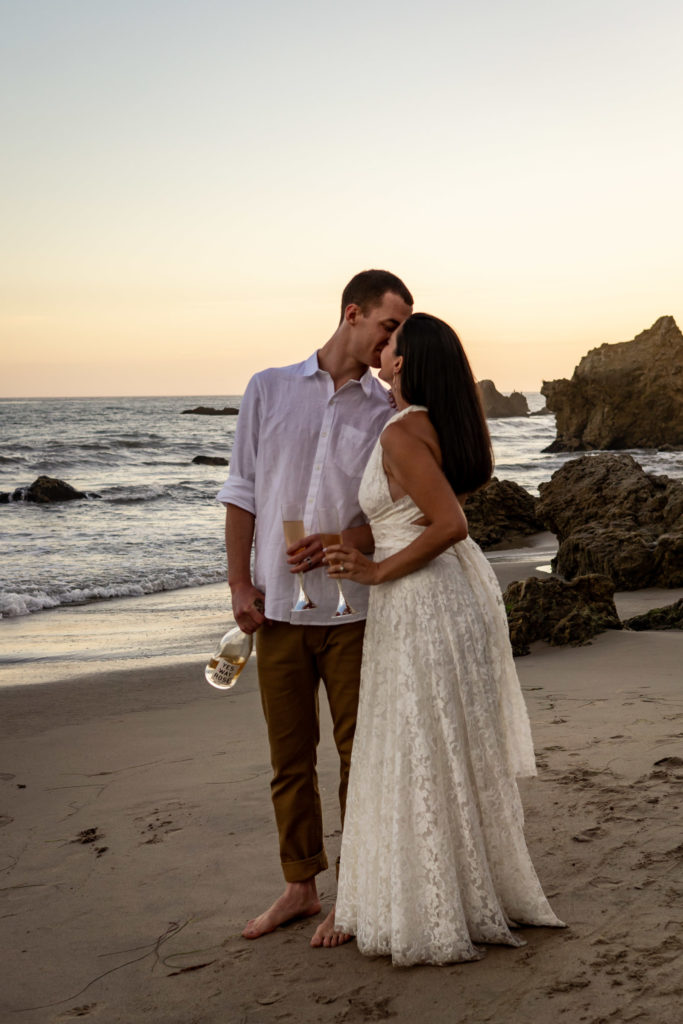 A man and woman in wedding clothes. They're kissing and holding champagne glasses during sunset on a rocky beach in California.