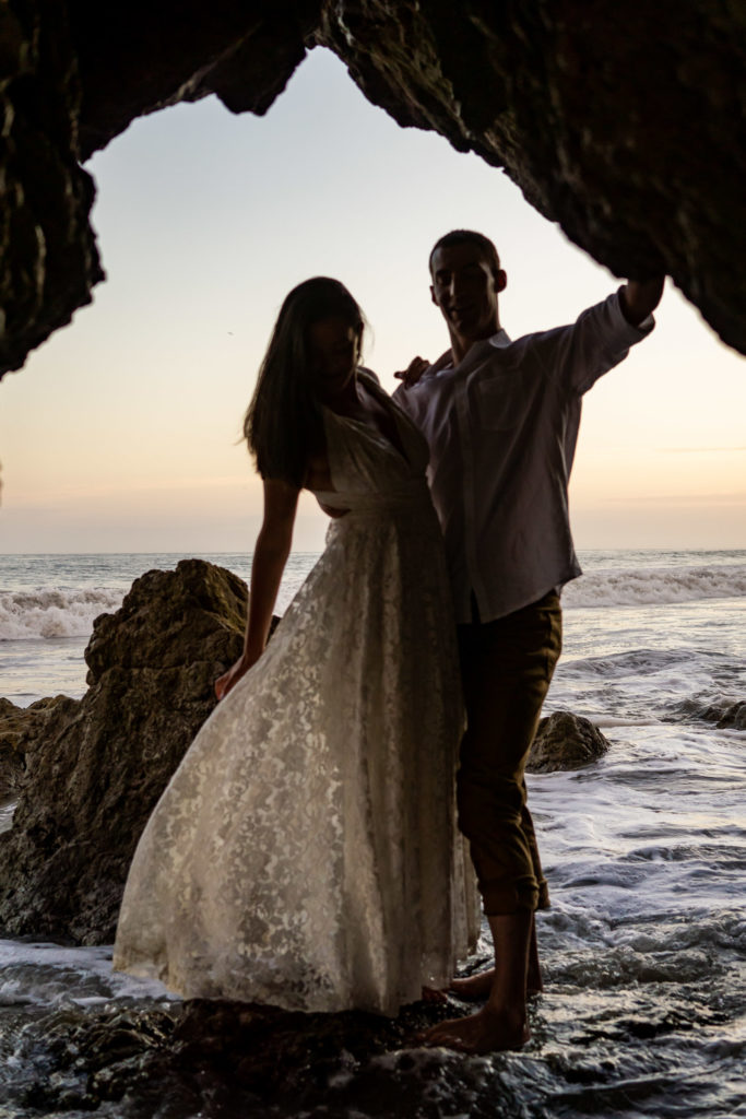 A bride and groom silhouetted while standing on a rock over the ocean. The lace dress is flowing in the wind. Photo by Gabby Jockers Photography. California destination wedding, California elopement, California elopement inspiration, California beach elopement, El Matador beach elopement, El Matador elopement ideas, El Matador Beach elopement inspiration, California wedding inspiration, elopement inspiration, elopement ideas, elopement photography, beach elopement, destination elopement, destination wedding, adventure elopement, adventurous elopement, hiking elopement, Colorado elopement, Colorado elopement photographer