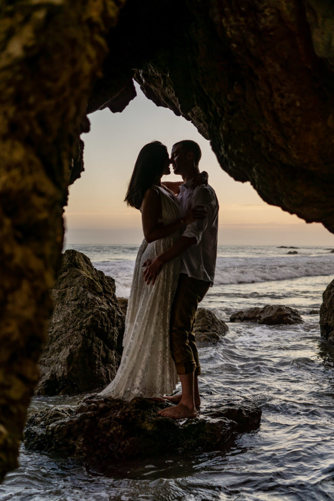 A bride and groom silhouetted while standing on a rock over the ocean. Photo by Gabby Jockers Photography. California destination wedding, California elopement, California elopement inspiration, California beach elopement, El Matador beach elopement, El Matador elopement ideas, El Matador Beach elopement inspiration, California wedding inspiration, elopement inspiration, elopement ideas, elopement photography, beach elopement, destination elopement, destination wedding, adventure elopement, adventurous elopement, hiking elopement, Colorado elopement, Colorado elopement photographer