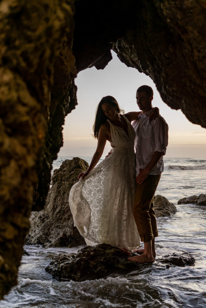 A bride and groom silhouetted while standing on a rock over the ocean. The bride's lace dress is flowing in the wind. Photo by Gabby Jockers Photography. California destination wedding, California elopement, California elopement inspiration, California beach elopement, El Matador beach elopement, El Matador elopement ideas, El Matador Beach elopement inspiration, California wedding inspiration, elopement inspiration, elopement ideas, elopement photography, beach elopement, destination elopement, destination wedding, adventure elopement, adventurous elopement, hiking elopement, Colorado elopement, Colorado elopement photographer