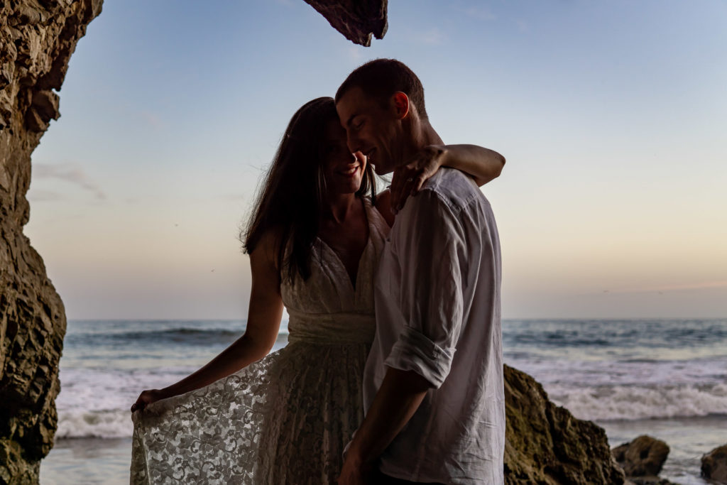 A couple posing in the caves on El Matador Beach. They're in shadows but you can see their smiles and the lace pattern of the bride's lace dress. Photo by Gabby Jockers Photography. California destination wedding, California elopement, California elopement inspiration, California beach elopement, El Matador beach elopement, El Matador elopement ideas, El Matador Beach elopement inspiration, California wedding inspiration, elopement inspiration, elopement ideas, elopement photography, beach elopement, destination elopement, destination wedding, adventure elopement, adventurous elopement, hiking elopement, Colorado elopement, Colorado elopement photographer