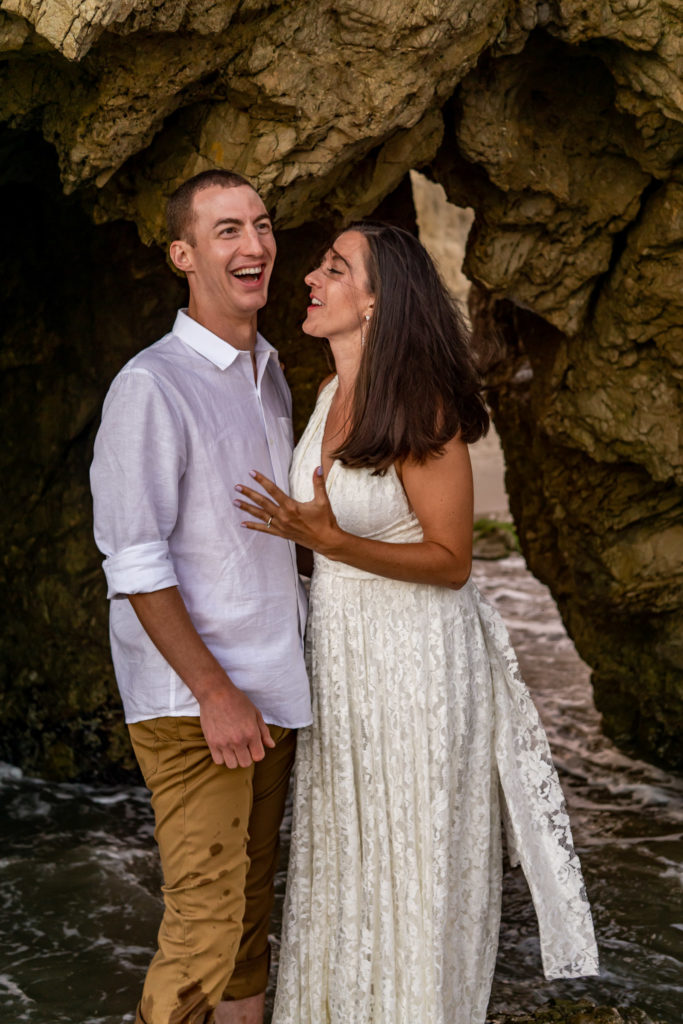 A couple laughing and playing together in the caves on the beach at El Matador beach. Photo by Gabby Jockers Photography. California destination wedding, California elopement, California elopement inspiration, California beach elopement, El Matador beach elopement, El Matador elopement ideas, El Matador Beach elopement inspiration, California wedding inspiration, elopement inspiration, elopement ideas, elopement photography, beach elopement, destination elopement, destination wedding, adventure elopement, adventurous elopement, hiking elopement, Colorado elopement, Colorado elopement photographer