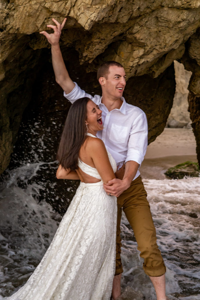 A couple laughing and playing together in the caves on the beach at El Matador beach. Waves are splashing on them and they're laughing. Photo by Gabby Jockers Photography. California destination wedding, California elopement, California elopement inspiration, California beach elopement, El Matador beach elopement, El Matador elopement ideas, El Matador Beach elopement inspiration, California wedding inspiration, elopement inspiration, elopement ideas, elopement photography, beach elopement, destination elopement, destination wedding, adventure elopement, adventurous elopement, hiking elopement, Colorado elopement, Colorado elopement photographer