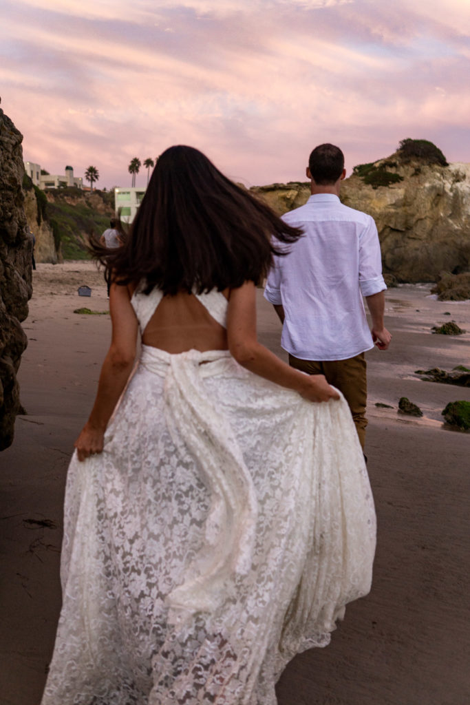 A man is running toward the beach cliffs while his wife runs behind while holding up her lace dress. Photo by Gabby Jockers Photography. California destination wedding, California elopement, California elopement inspiration, California beach elopement, El Matador beach elopement, El Matador elopement ideas, El Matador Beach elopement inspiration, California wedding inspiration, elopement inspiration, elopement ideas, elopement photography, beach elopement, destination elopement, destination wedding, adventure elopement, adventurous elopement, hiking elopement, Colorado elopement, Colorado elopement photographer