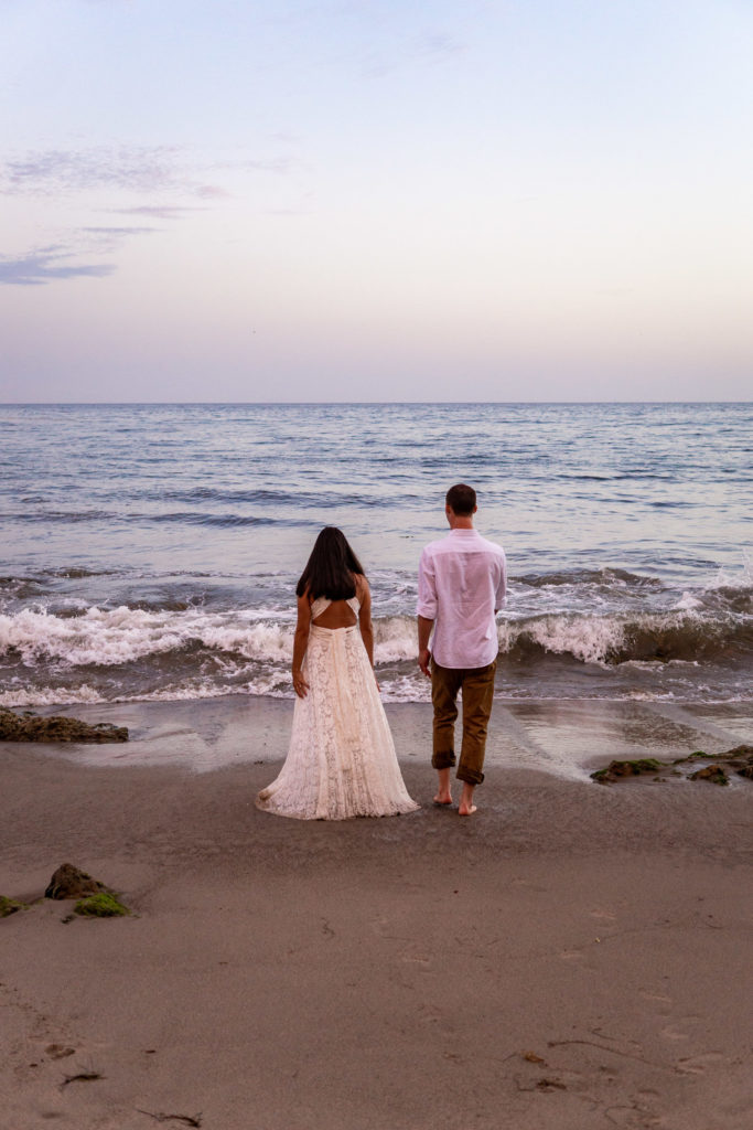 A bride and groom walking into the pacific ocean side by side. Photo by Gabby Jockers Photography. California destination wedding, California elopement, California elopement inspiration, California beach elopement, El Matador beach elopement, El Matador elopement ideas, El Matador Beach elopement inspiration, California wedding inspiration, elopement inspiration, elopement ideas, elopement photography, beach elopement, destination elopement, destination wedding, adventure elopement, adventurous elopement, hiking elopement, Colorado elopement, Colorado elopement photographer