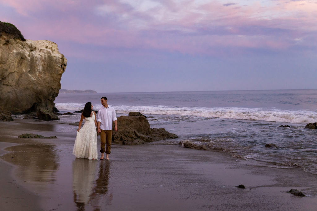 A bride in a flowy white lace dress walks down the beach with her groom during a pink and dusky blue sunset at El Matador Beach in California. Photo by Gabby Jockers Photography. California destination wedding, California elopement, California elopement inspiration, California beach elopement, El Matador beach elopement, El Matador elopement ideas, El Matador Beach elopement inspiration, California wedding inspiration, elopement inspiration, elopement ideas, elopement photography, beach elopement, destination elopement, destination wedding, adventure elopement, adventurous elopement, hiking elopement, Colorado elopement, Colorado elopement photographer