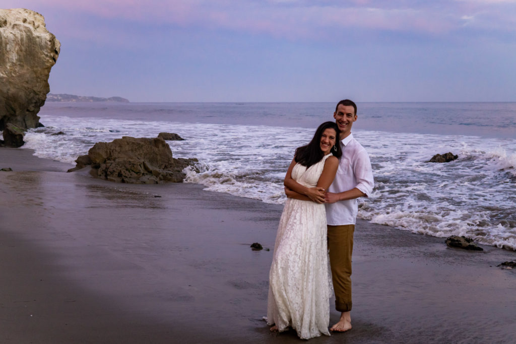 On the pink sunset beach of California, a tall groom holds onto his bride with long dark hair in her white lace dress. Photo by Gabby Jockers Photography. California destination wedding, California elopement, California elopement inspiration, California beach elopement, El Matador beach elopement, El Matador elopement ideas, El Matador Beach elopement inspiration, California wedding inspiration, elopement inspiration, elopement ideas, elopement photography, beach elopement, destination elopement, destination wedding, adventure elopement, adventurous elopement, hiking elopement, Colorado elopement, Colorado elopement photographer
