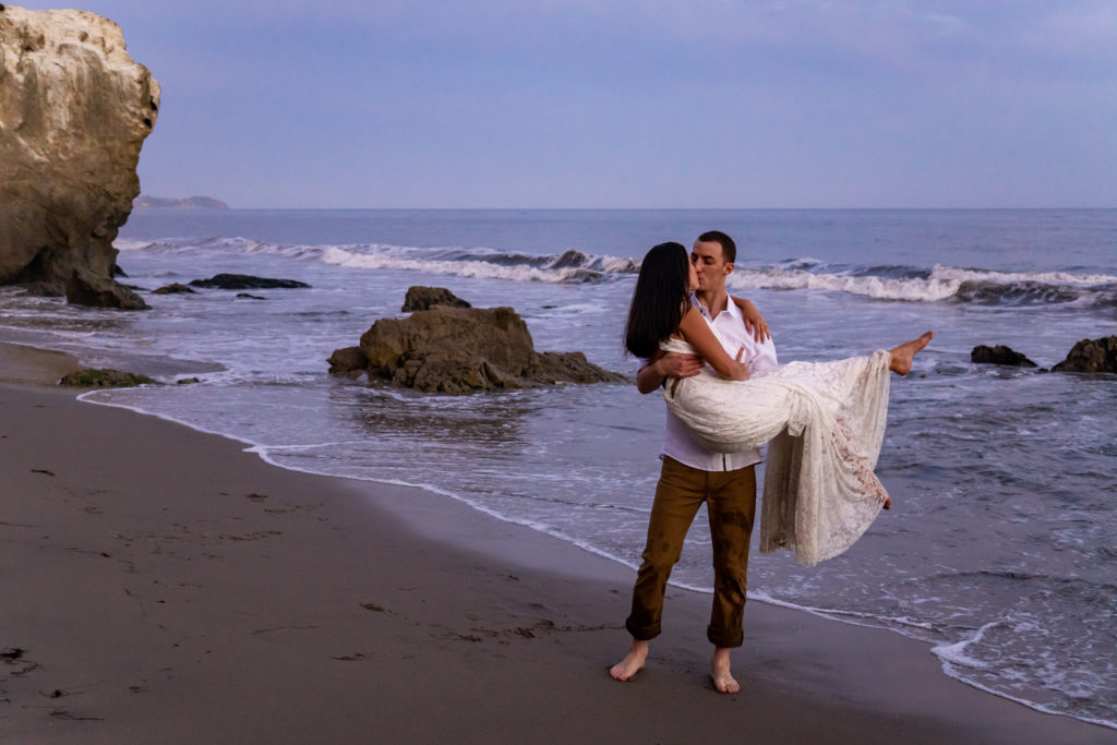 On the pink sunset beach of California, a tall groom holds up his bride with long dark hair in her white lace dress. Photo by Gabby Jockers Photography. California destination wedding, California elopement, California elopement inspiration, California beach elopement, El Matador beach elopement, El Matador elopement ideas, El Matador Beach elopement inspiration, California wedding inspiration, elopement inspiration, elopement ideas, elopement photography, beach elopement, destination elopement, destination wedding, adventure elopement, adventurous elopement, hiking elopement, Colorado elopement, Colorado elopement photographer