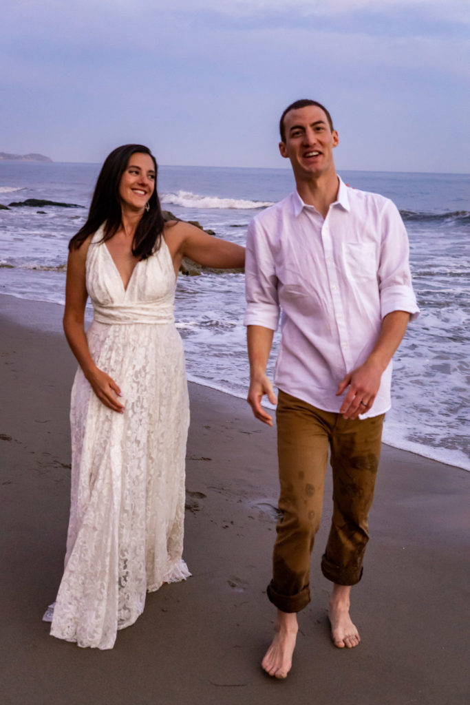 A bride ina flowy lace wedding dress happily walking on the beach with her groom. Photo by Gabby Jockers Photography. California destination wedding, California elopement, California elopement inspiration, California beach elopement, El Matador beach elopement, El Matador elopement ideas, El Matador Beach elopement inspiration, California wedding inspiration, elopement inspiration, elopement ideas, elopement photography, beach elopement, destination elopement, destination wedding, adventure elopement, adventurous elopement, hiking elopement, Colorado elopement, Colorado elopement photographer