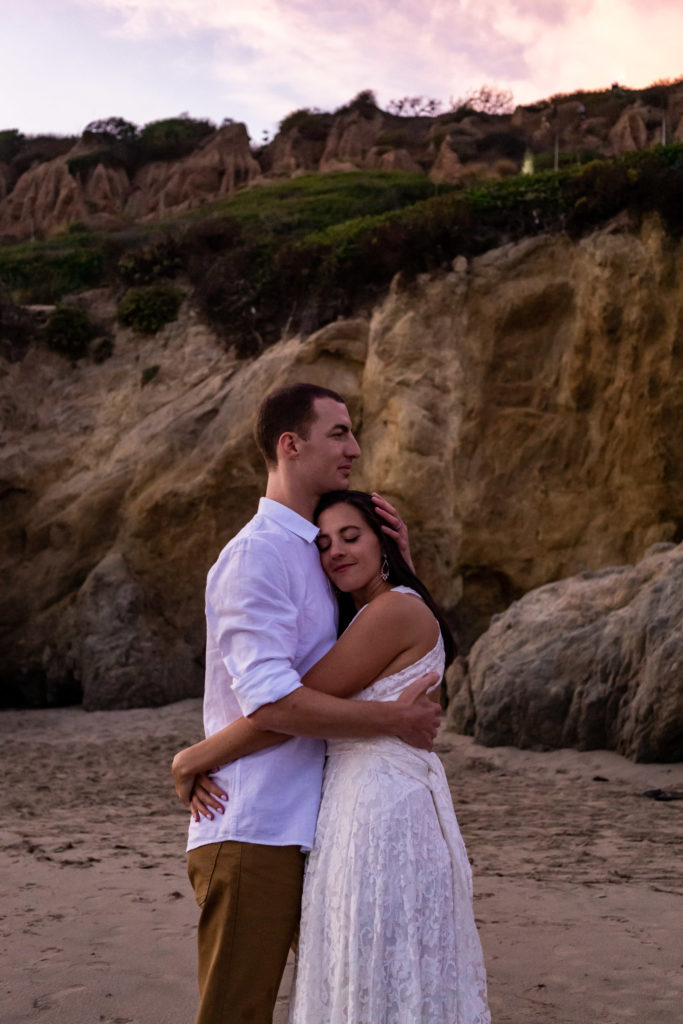 A tender embrace between bride and groom in front of the El Matador cliffs at sunset. The bride's wearing a soft lace dress and the groom wearing a white shirt and brown pants. Photo by Gabby Jockers Photography. California destination wedding, California elopement, California elopement inspiration, California beach elopement, El Matador beach elopement, El Matador elopement ideas, El Matador Beach elopement inspiration, California wedding inspiration, elopement inspiration, elopement ideas, elopement photography, beach elopement, destination elopement, destination wedding, adventure elopement, adventurous elopement, hiking elopement, Colorado elopement, Colorado elopement photographer