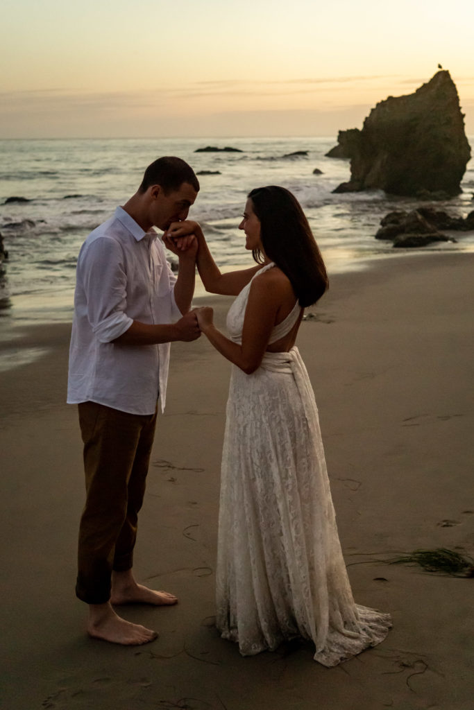 A bride wearing a flowy lace dress kissing with her groom at sunset on el matador beach. Photo by Gabby Jockers Photography. California destination wedding, California elopement, California elopement inspiration, California beach elopement, El Matador beach elopement, El Matador elopement ideas, El Matador Beach elopement inspiration, California wedding inspiration, elopement inspiration, elopement ideas, elopement photography, beach elopement, destination elopement, destination wedding, adventure elopement, adventurous elopement, hiking elopement, Colorado elopement, Colorado elopement photographer