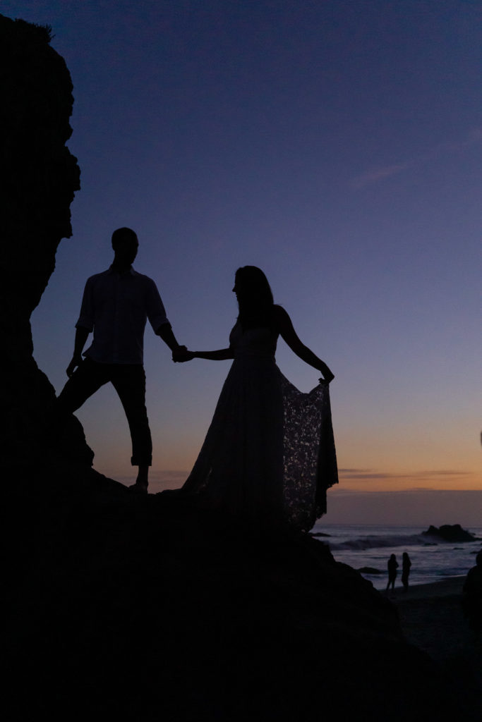 A silhouetted couple against the beach sunset standing on the rocks on el matador beach in california. Photo by Gabby Jockers Photography. California destination wedding, California elopement, California elopement inspiration, California beach elopement, El Matador beach elopement, El Matador elopement ideas, El Matador Beach elopement inspiration, California wedding inspiration, elopement inspiration, elopement ideas, elopement photography, beach elopement, destination elopement, destination wedding, adventure elopement, adventurous elopement, hiking elopement, Colorado elopement, Colorado elopement photographer