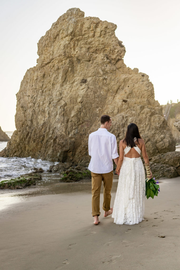 A man and woman, the man in white and the woman in an ivory lace dress, They're on a beautiful California beach. Photo by Gabby Jockers.