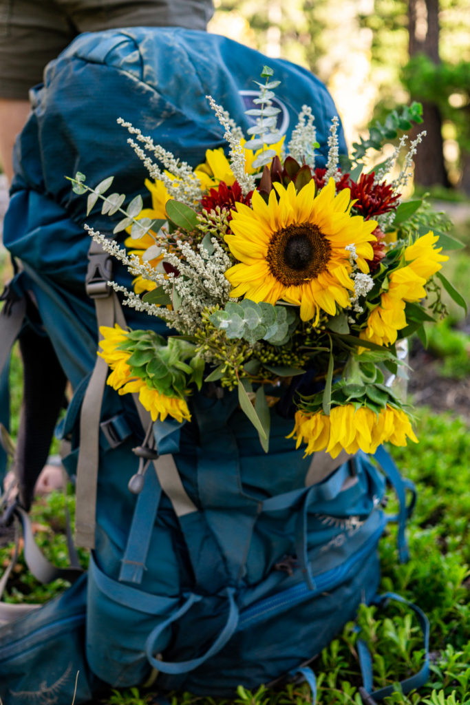 Teal hiking backpack with yellow sunflower bouquet tucked inside.