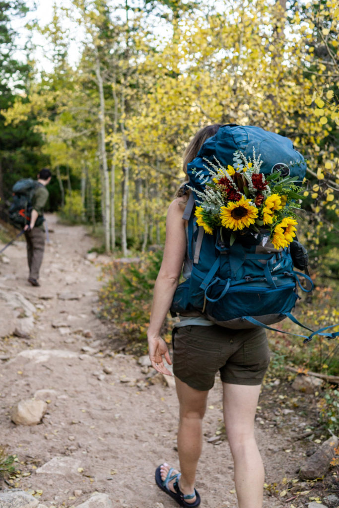 A woman walking down a hiking down a trail with a bright blue hiking backpack with a bright yellow bouquet of sunflowers poking out. Photo by Gabby Jockers Photography. sunflower bouquet, dog elopement, hiking with flowers, colorado elopement, colorado elopement photography, golden gate canyon state park, sunset elopement, hiking elopement, fall wedding, mountain wedding, adventure photos, mountain elopement, fall elopement, adventure elopement, denver colorado photographer, elopement photographer