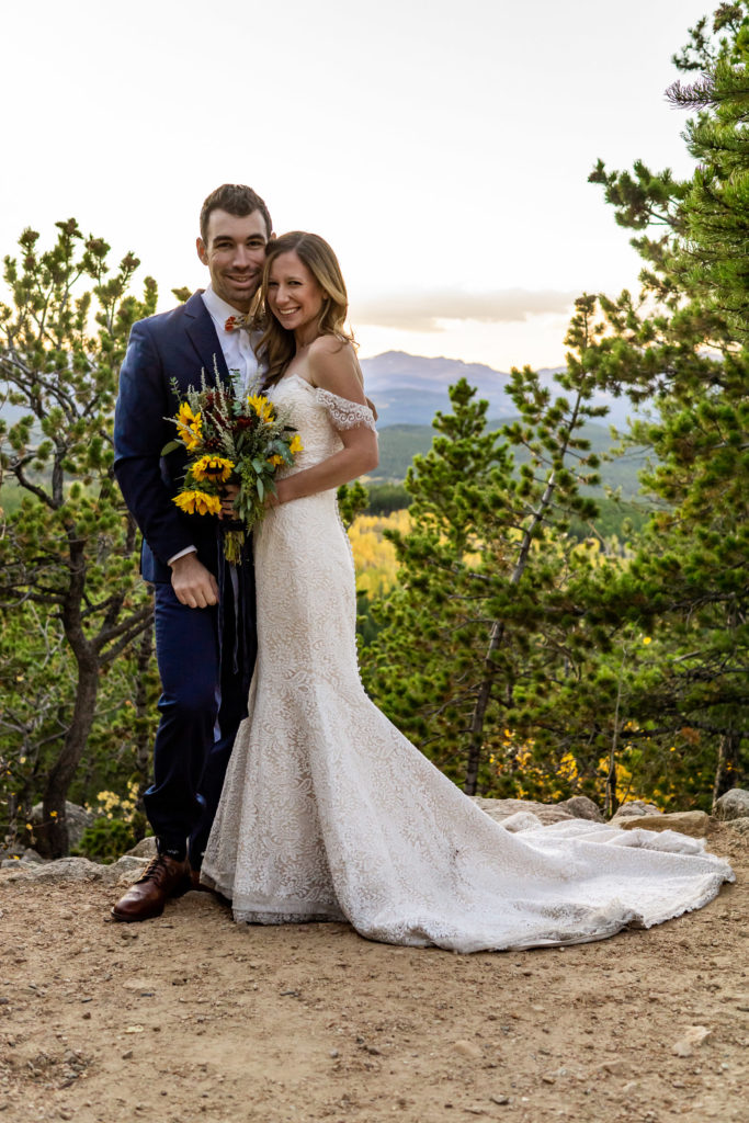 Young bride and groom hugging and looking at the camera in front of a mountain sunset at this fall mountain wedding. Bride has a yellow sunflower bouquet.