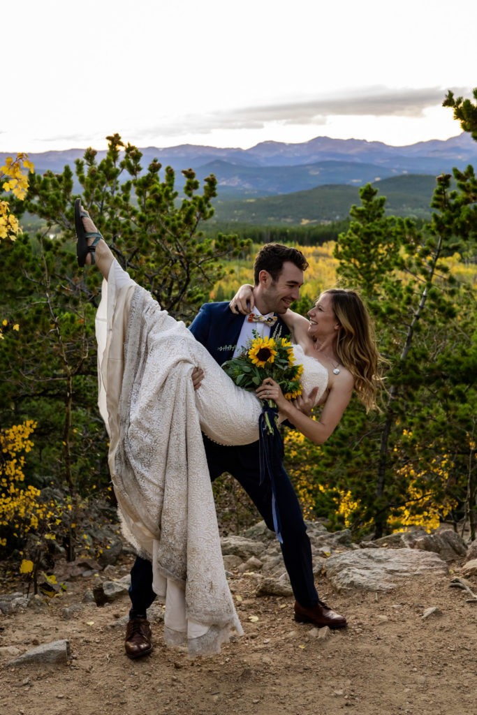 A stylish groom in a blue suit and bowtie and bride holding a sunflower bouquet in an aspen forest during the fall in the Colorado mountains. Photo by Gabby Jockers Photography. colorado elopement, colorado elopement photography, golden gate canyon state park, sunset elopement, hiking elopement, fall wedding, mountain wedding, adventure photos, mountain elopement, fall elopement, adventure elopement, denver colorado photographer, elopement photographer