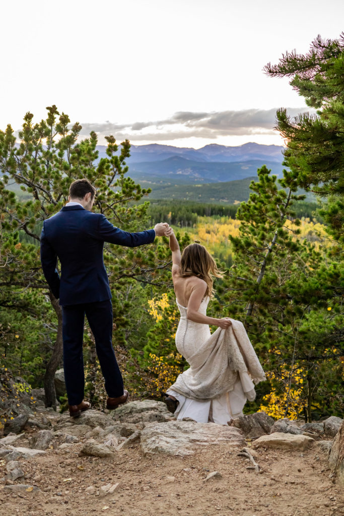 Young bride and groom climbing down rocks and holding hands in front of a mountain sunset at this fall mountain wedding