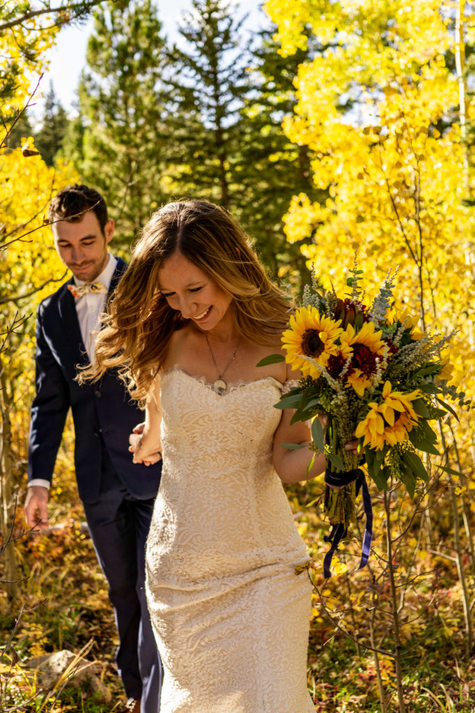 Bride leading a groom by hand through a yellow aspen forest in this fall mountain wedding. She's smiling hard and holding a yellow sunflower bouquet.