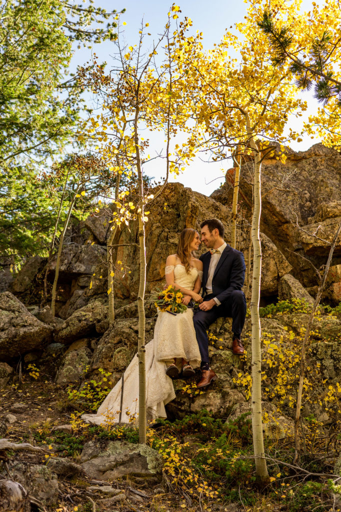 Bride and groom sitting side-by-side on a shaded boulder surrounded by aspens. A yellow sunflower bouquet sits on the bride's lap. Their noses are almost touching.