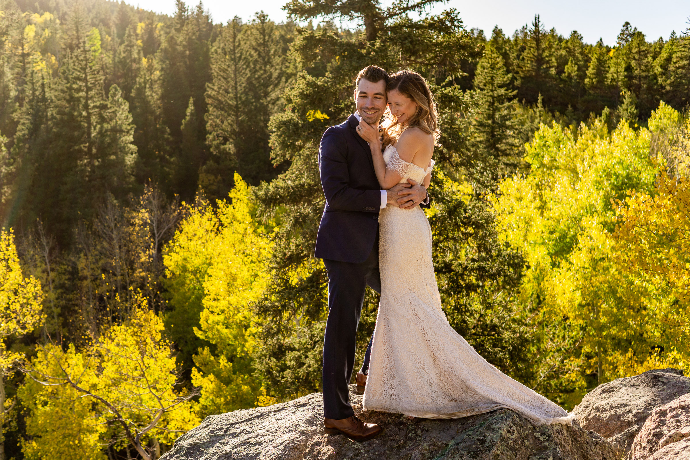 A bride and groom romantically embracing in front of a golden aspen forest during fall in the Colorado mountains. Photo by Gabby Jockers Photography. colorado elopement, colorado elopement photography, golden gate canyon state park, sunset elopement, hiking elopement, fall wedding, mountain wedding, adventure photos, mountain elopement, fall elopement, adventure elopement, denver colorado photographer, elopement photographer
