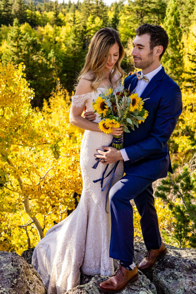 Bride and groom standing on a boulder over a yellow aspen forest. He's holding he waist and she's holding a yellow sunflower bouquet.