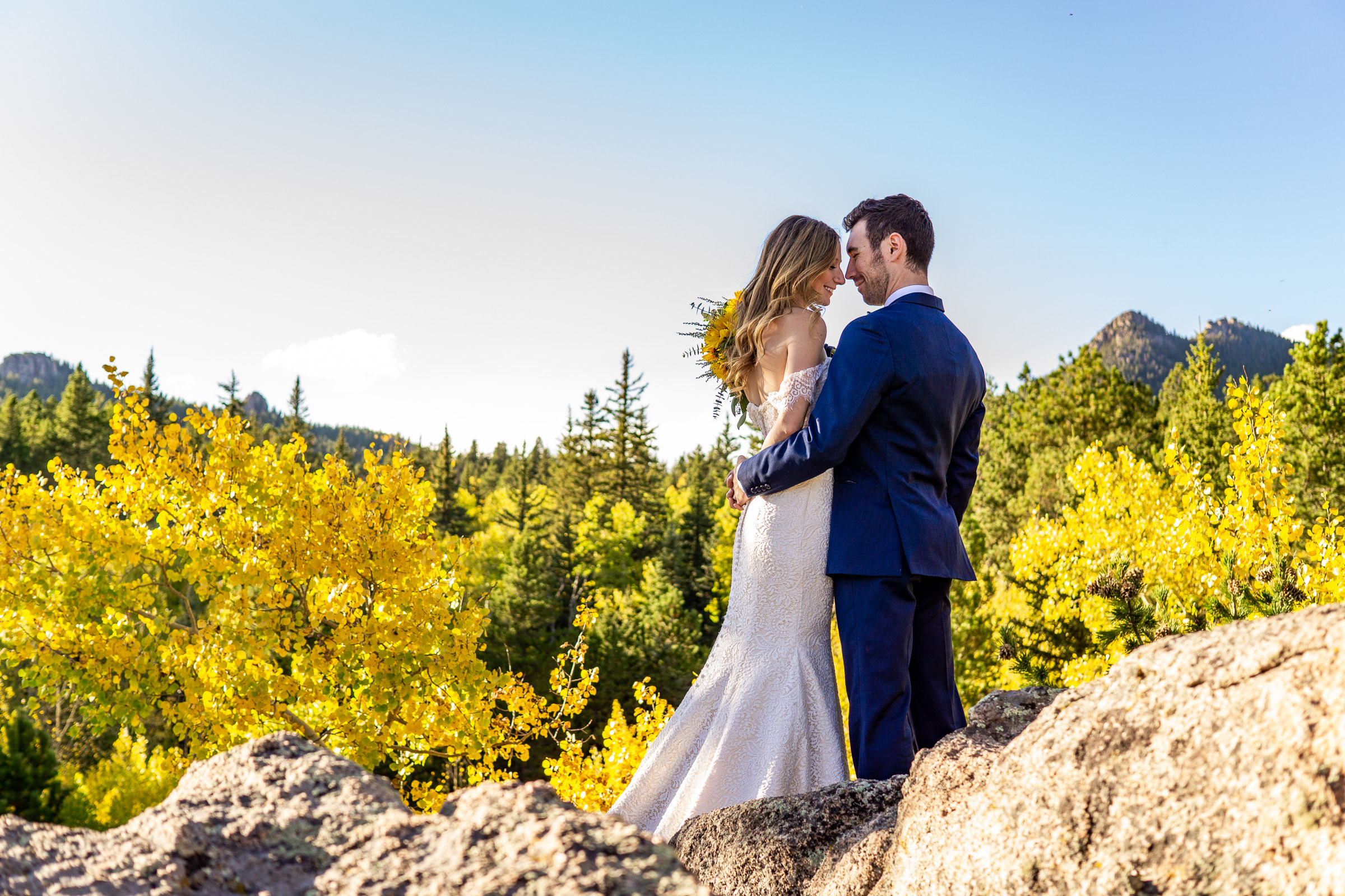 A bride (with a sunflower bouquet) and groom (wearing a blue wedding suit) embracing in front of a golden aspen forest and mountain. Photo by Gabby Jockers Photography. colorado elopement, colorado elopement photography, golden gate canyon state park, sunset elopement, hiking elopement, fall wedding, mountain wedding, adventure photos, mountain elopement, fall elopement, adventure elopement, denver colorado photographer, elopement photographer