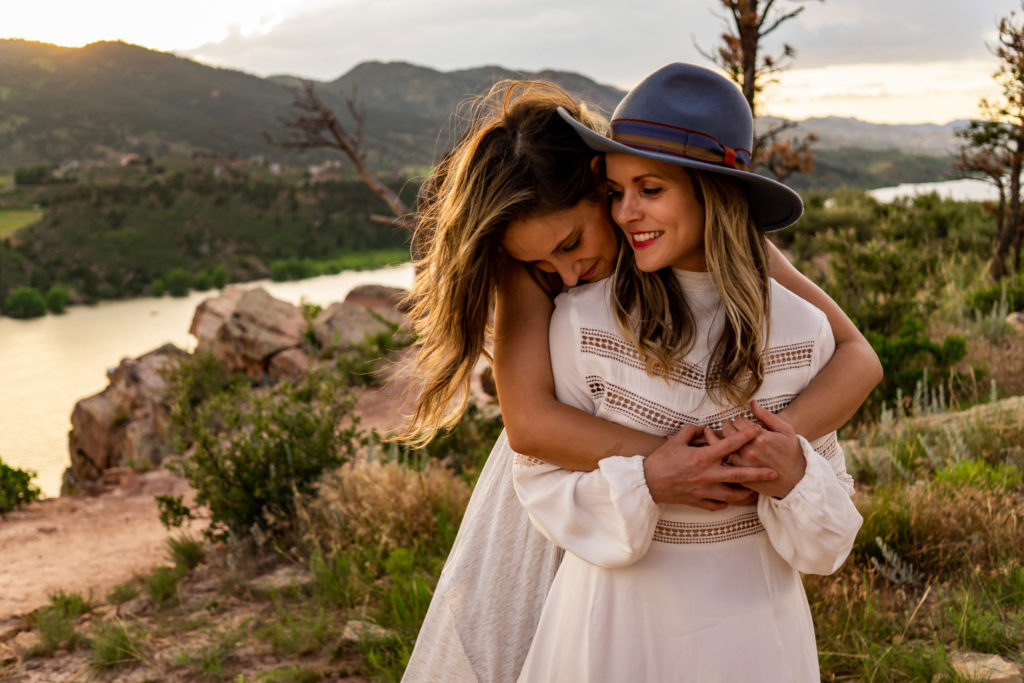 Two women in flowy white dresses embracing during sunset in front of Horsetooth Reservoir in Colorado.