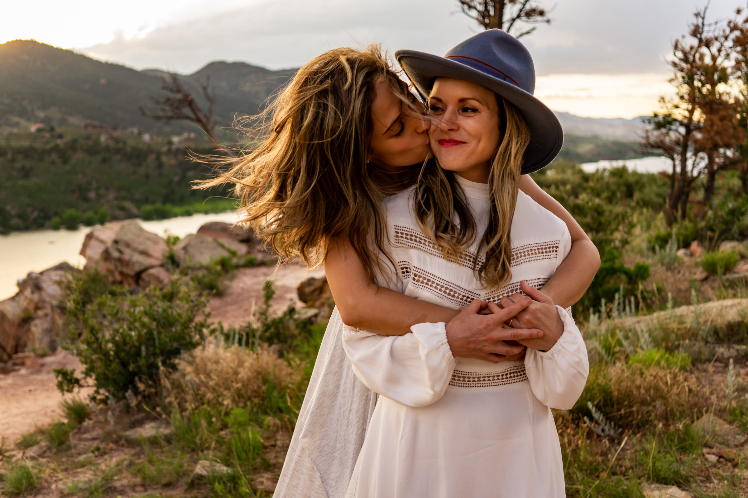 Two women wearing white dresses embracing and playing in front of a reservoir at sunset. Photo by Gabby Jockers Photography. Horsetooth reservoir elopement, horsetooth reservoir elopement photography, fort collins elopement, colorado elopement, colorado elopement photography, horsetooth reservoir engagement photos, horsetooth reservoir engagement session, sunset engagement session, sunset elopement, hiking elopement, hiking engagement, adventure photos, adventure session, LGBT elopement, adventure elopement, denver colorado photographer