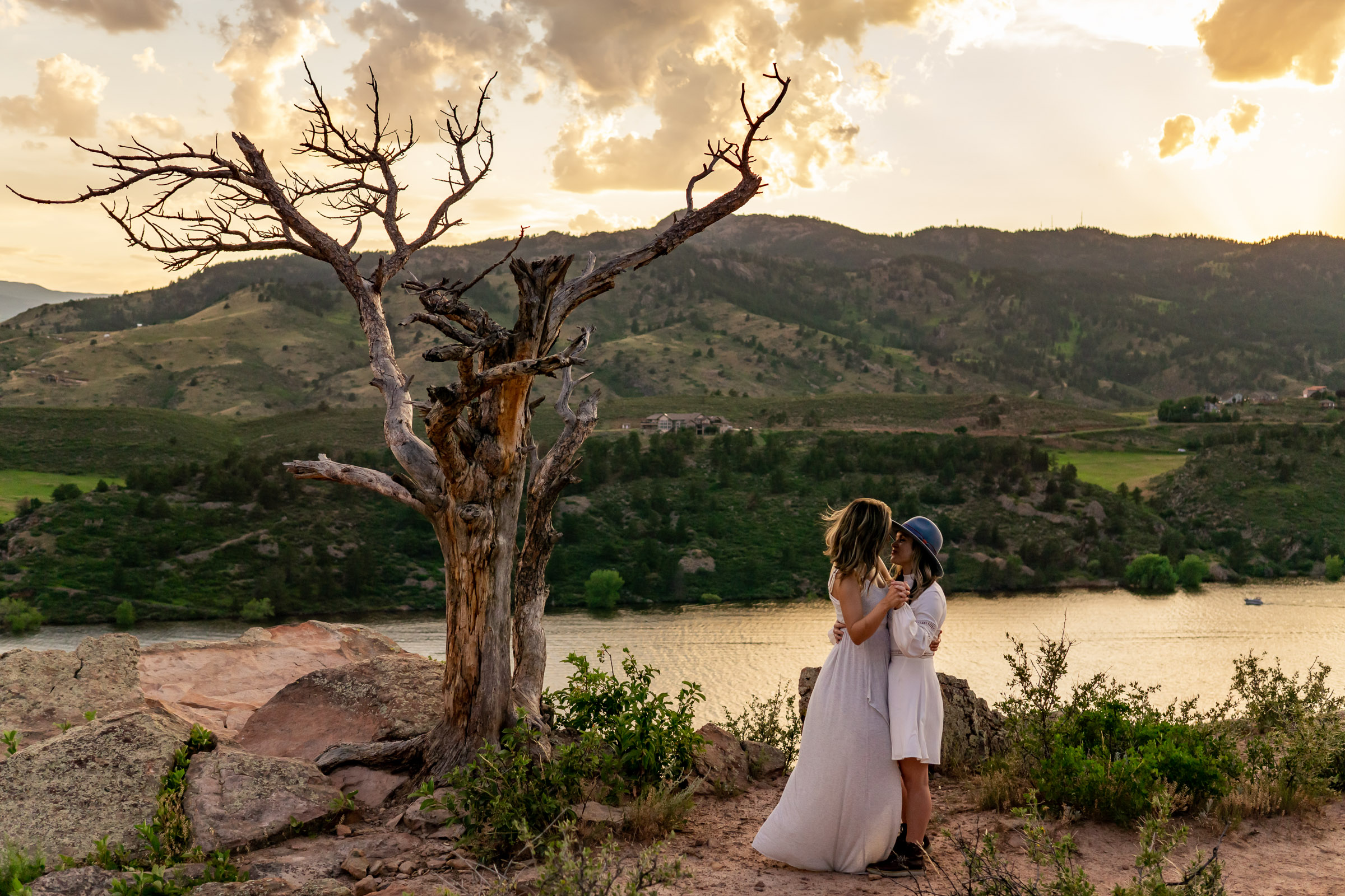 Two women wearing white dresses dancing in front of a reservoir at sunset. Photo by Gabby Jockers Photography. Horsetooth reservoir elopement, horsetooth reservoir elopement photography, fort collins elopement, colorado elopement, colorado elopement photography, horsetooth reservoir engagement photos, horsetooth reservoir engagement session, sunset engagement session, sunset elopement, hiking elopement, hiking engagement, adventure photos, adventure session, LGBT elopement, adventure elopement, denver colorado photographer