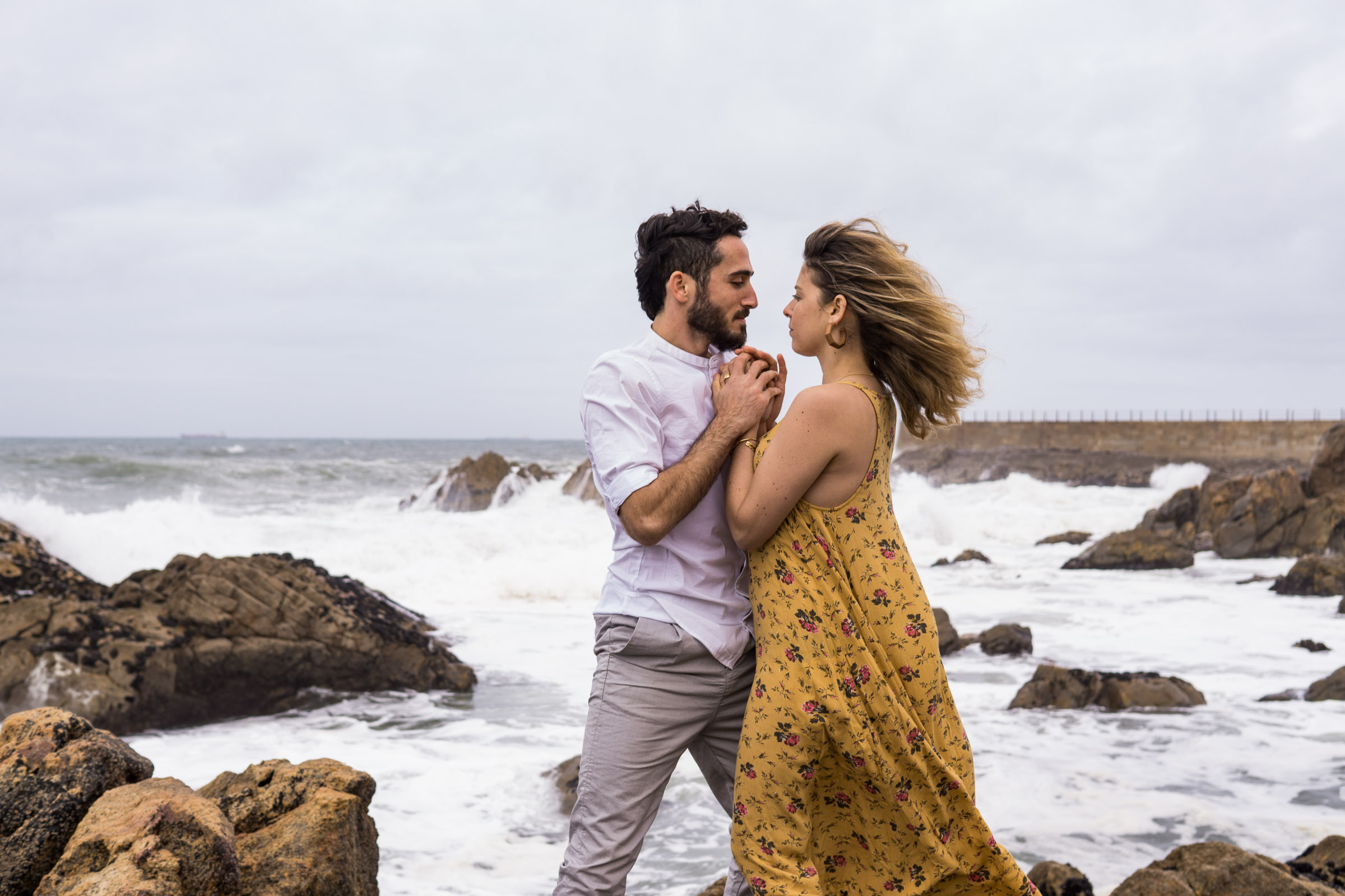 Couple huddled together on the rocks on the edge of the Atlantic Ocean in Portugal in fierce wind.