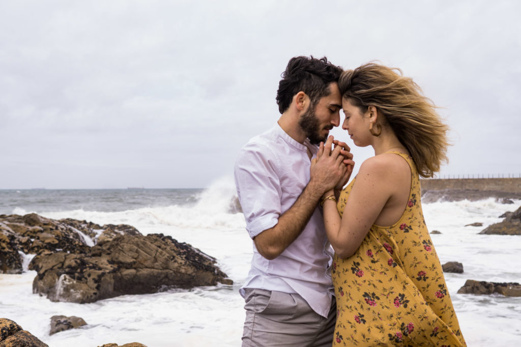 A man and woman with foreheads together and hands tangled in front of them on the rocky beach in Porto Portugal.