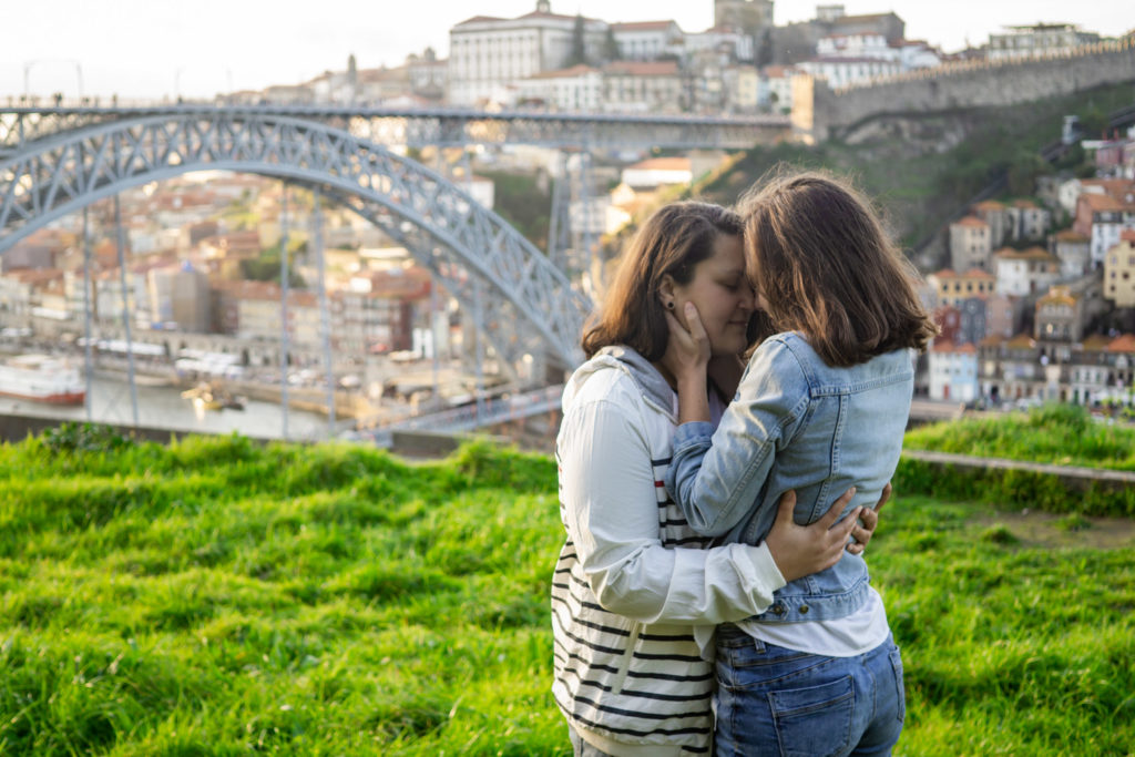 Two women embracing in front of a bridge in Porto, Portugal.