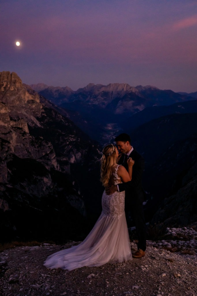 Couple in wedding clothes snuggling under the full moon in front of a beautiful mountain valley. Photo by Gabby Jockers Photography. Dolomites destination wedding, Dolomites elopement, Dolomites elopement inspiration, Milan elopement, Tre Cime elopement, Italy elopement ideas, Italy elopement inspiration, Italy wedding inspiration, elopement inspiration, elopement ideas, elopement photography, mountain elopement, destination elopement, destination wedding, adventure elopement, adventurous elopement, hiking elopement, Colorado elopement, Colorado elopement photographer