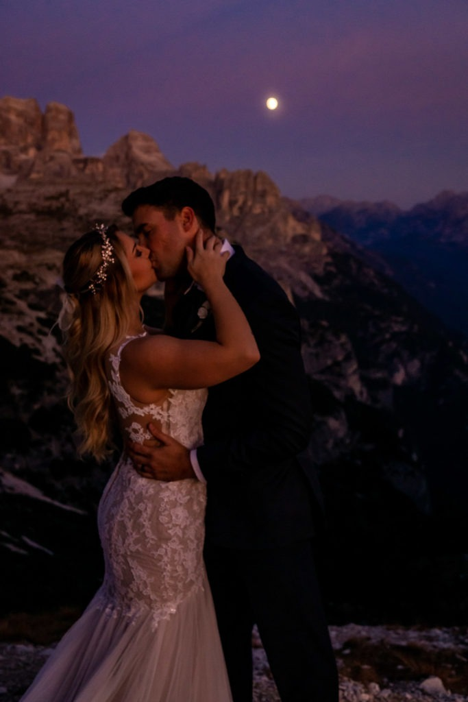 Couple in wedding clothes kissing under the full moon in front of a beautiful mountain valley. Photo by Gabby Jockers Photography. Dolomites destination wedding, Dolomites elopement, Dolomites elopement inspiration, Milan elopement, Tre Cime elopement, Italy elopement ideas, Italy elopement inspiration, Italy wedding inspiration, elopement inspiration, elopement ideas, elopement photography, mountain elopement, destination elopement, destination wedding, adventure elopement, adventurous elopement, hiking elopement, Colorado elopement, Colorado elopement photographer