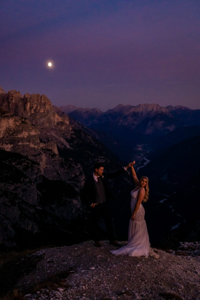 Couple in wedding clothes dancing under the full moon in front of a beautiful mountain valley. Photo by Gabby Jockers Photography. Dolomites destination wedding, Dolomites elopement, Dolomites elopement inspiration, Milan elopement, Tre Cime elopement, Italy elopement ideas, Italy elopement inspiration, Italy wedding inspiration, elopement inspiration, elopement ideas, elopement photography, mountain elopement, destination elopement, destination wedding, adventure elopement, adventurous elopement, hiking elopement, Colorado elopement, Colorado elopement photographer