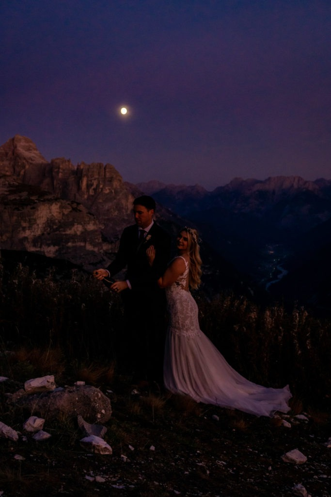 Couple in wedding clothes popping champagne under a full moon during blue hour in the Dolomites. Photo by Gabby Jockers Photography. Dolomites destination wedding, Dolomites elopement, Dolomites elopement inspiration, Milan elopement, Tre Cime elopement, Italy elopement ideas, Italy elopement inspiration, Italy wedding inspiration, elopement inspiration, elopement ideas, elopement photography, mountain elopement, destination elopement, destination wedding, adventure elopement, adventurous elopement, hiking elopement, Colorado elopement, Colorado elopement photographer