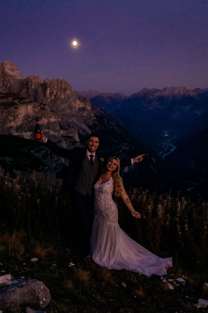 Couple in wedding clothes cheering under a full moon during blue hour in the Dolomites. Photo by Gabby Jockers Photography. Dolomites destination wedding, Dolomites elopement, Dolomites elopement inspiration, Milan elopement, Tre Cime elopement, Italy elopement ideas, Italy elopement inspiration, Italy wedding inspiration, elopement inspiration, elopement ideas, elopement photography, mountain elopement, destination elopement, destination wedding, adventure elopement, adventurous elopement, hiking elopement, Colorado elopement, Colorado elopement photographer