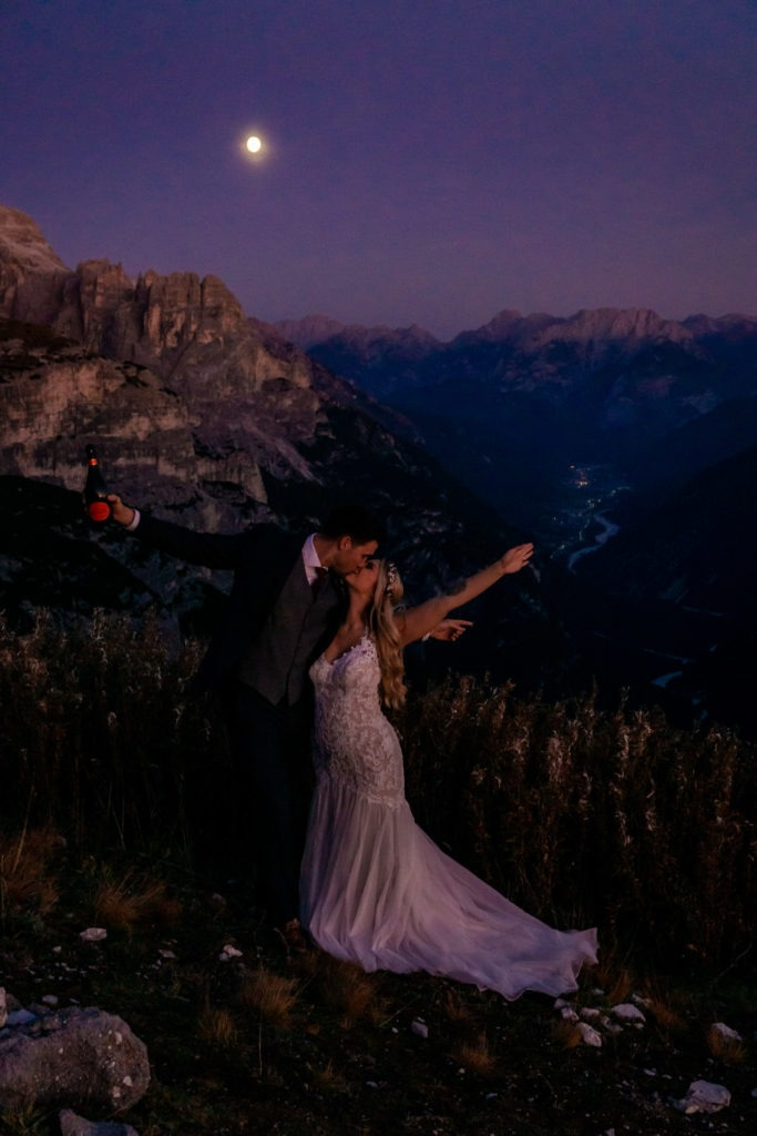 Couple in wedding clothes kissing while cheering under a full moon during blue hour in the Dolomites. Photo by Gabby Jockers Photography. Dolomites destination wedding, Dolomites elopement, Dolomites elopement inspiration, Milan elopement, Tre Cime elopement, Italy elopement ideas, Italy elopement inspiration, Italy wedding inspiration, elopement inspiration, elopement ideas, elopement photography, mountain elopement, destination elopement, destination wedding, adventure elopement, adventurous elopement, hiking elopement, Colorado elopement, Colorado elopement photographer
