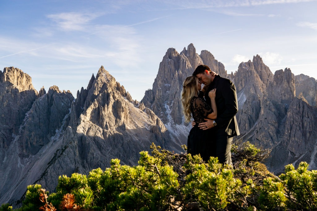 A man and woman in black embracing passionately in front of dramatic, craggy mountains in the Dolomites, Italy.