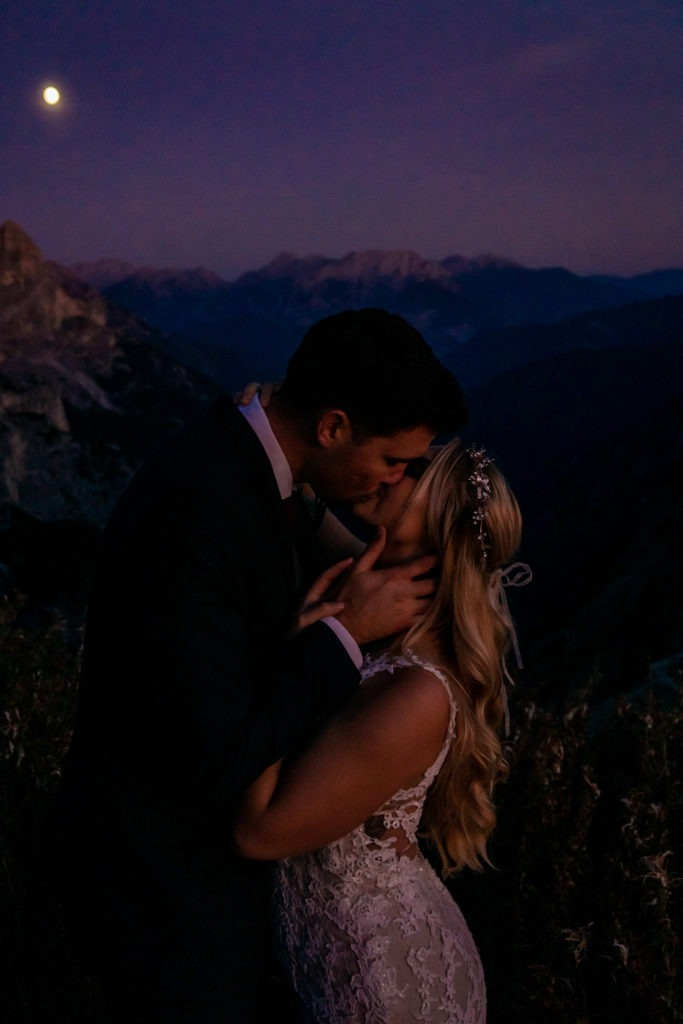 A man and woman in bridal clothes in a passionate embrace at dusk with the full moon.