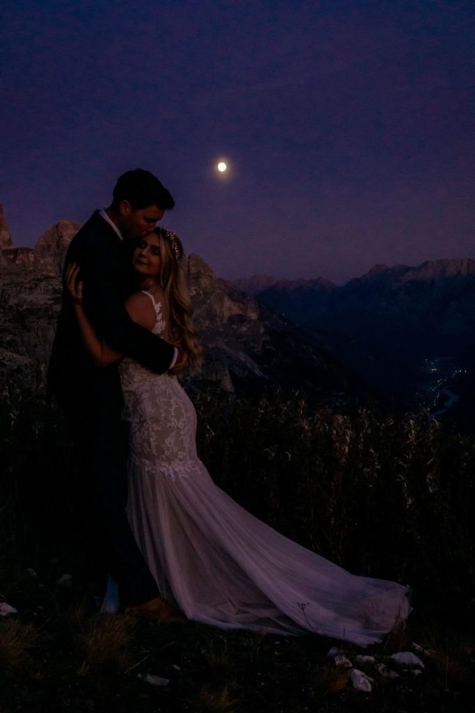 Couple in wedding clothes hugging under a full moon during blue hour in the Dolomites. Photo by Gabby Jockers Photography. Dolomites destination wedding, Dolomites elopement, Dolomites elopement inspiration, Milan elopement, Tre Cime elopement, Italy elopement ideas, Italy elopement inspiration, Italy wedding inspiration, elopement inspiration, elopement ideas, elopement photography, mountain elopement, destination elopement, destination wedding, adventure elopement, adventurous elopement, hiking elopement, Colorado elopement, Colorado elopement photographer