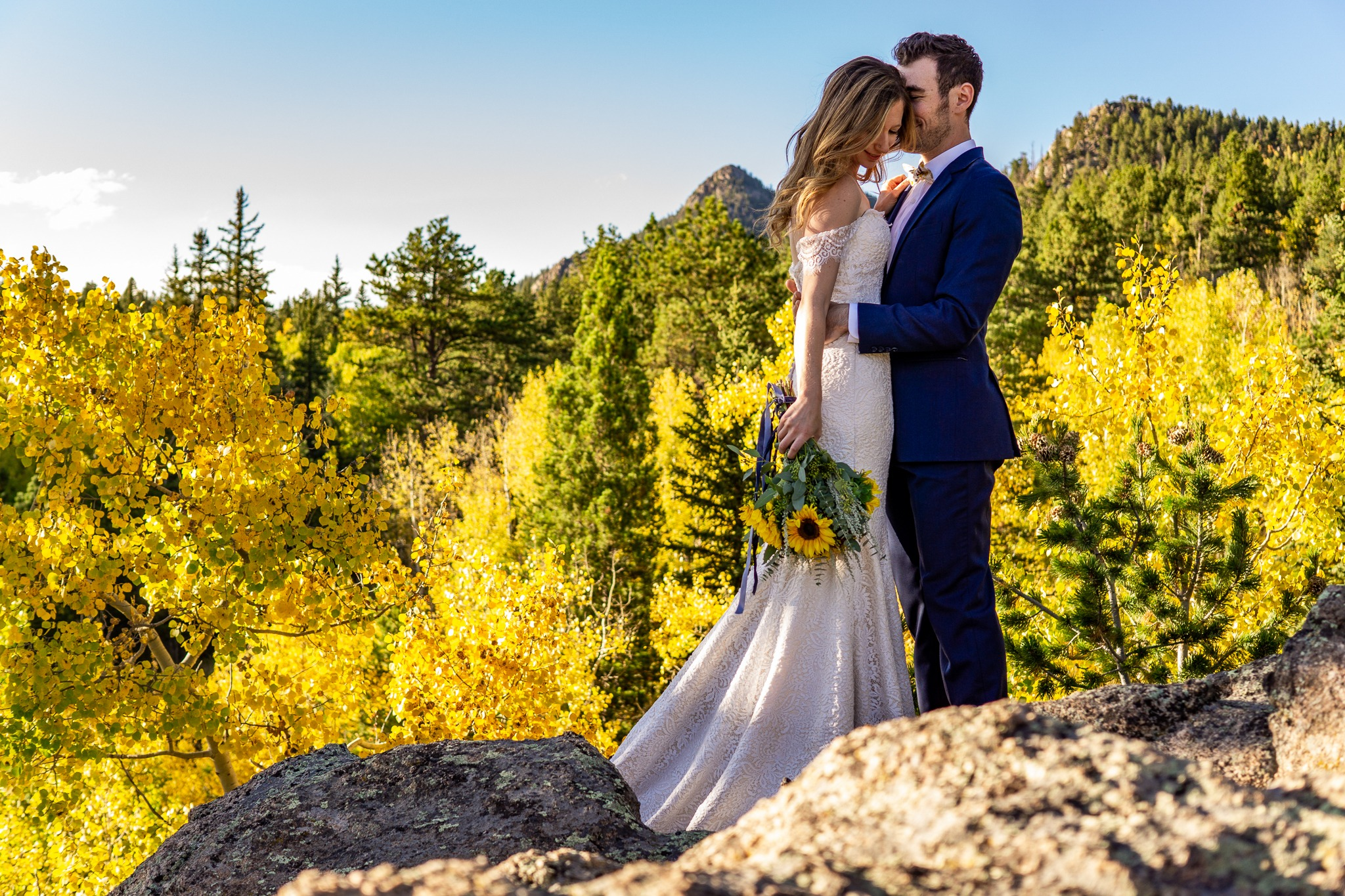 A man in a blue suit holding on to a woman in a bridal dress. They're standing on a boulder over a golden aspen forest in Colorado.