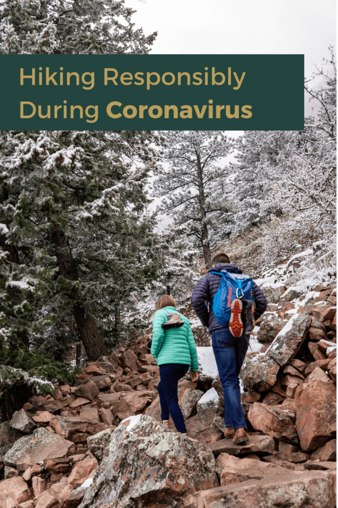 Hiking Responsibly During Coronavirus: Text overlay on a photograph of a couple wearing cold weather gear hiking up a rocky area toward some snowy trees in Colorado. Photo by Gabby Jockers Photography, Colorado elopement photographer.