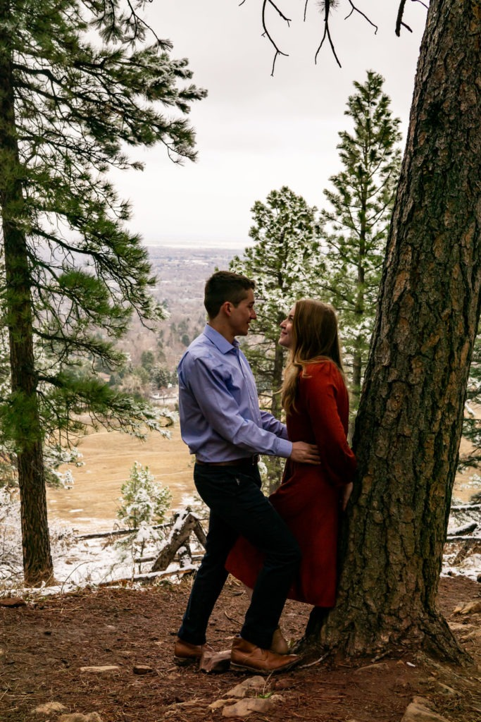A women leans against a tree as her fiance gets close in a snowy forest during this Boulder engagement session by Gabby Jockers Photography. boulder engagement photography, boulder engagement photos, boulder engagement session, chautauqua park engagement photos, chautauqua park engagement session, chautauqua park photography, Flatirons engagement photos, snowy engagement photos, snowy engagement session, hiking engagement, adventure photos, adventure session, couples photos