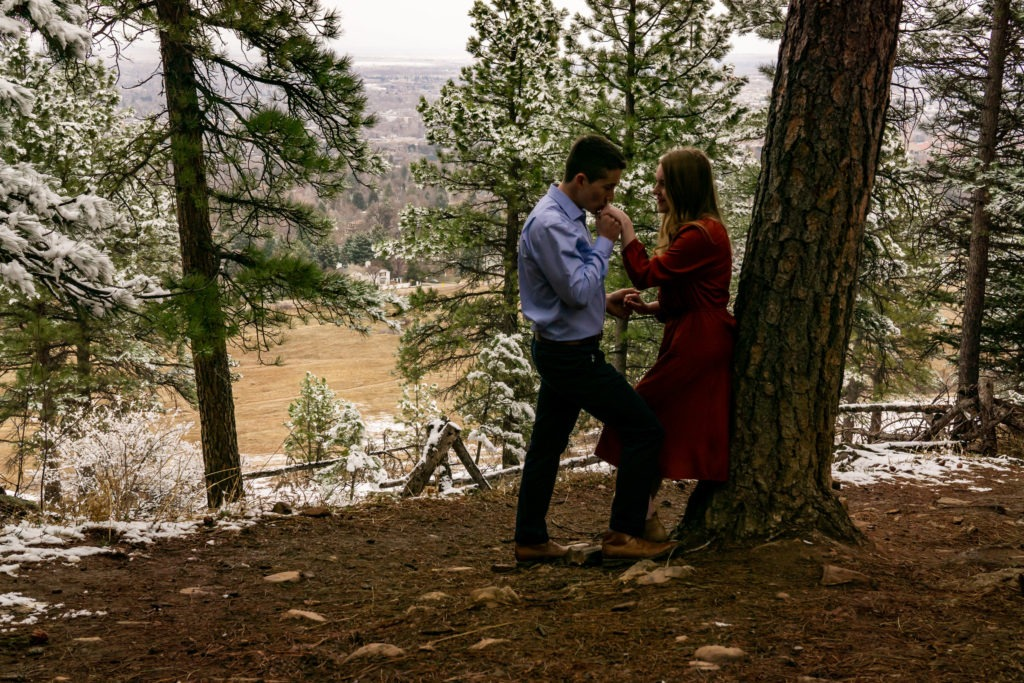 A man kissing his fiance's hand as she leans against a tree in a snowy forest during this Boulder engagement session by Gabby Jockers Photography. boulder engagement photography, boulder engagement photos, boulder engagement session, chautauqua park engagement photos, chautauqua park engagement session, chautauqua park photography, Flatirons engagement photos, snowy engagement photos, snowy engagement session, hiking engagement, adventure photos, adventure session, couples photos