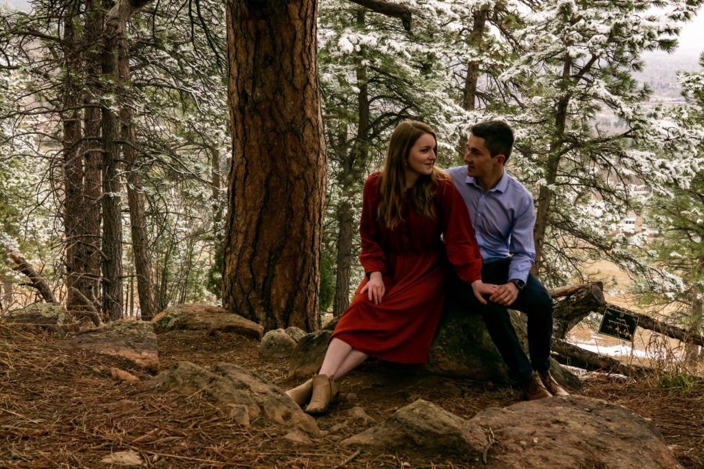 A couple sitting together on a rock in a snowy forest during this Boulder engagement session by Gabby Jockers Photography. boulder engagement photography, boulder engagement photos, boulder engagement session, chautauqua park engagement photos, chautauqua park engagement session, chautauqua park photography, Flatirons engagement photos, snowy engagement photos, snowy engagement session, hiking engagement, adventure photos, adventure session, couples photos