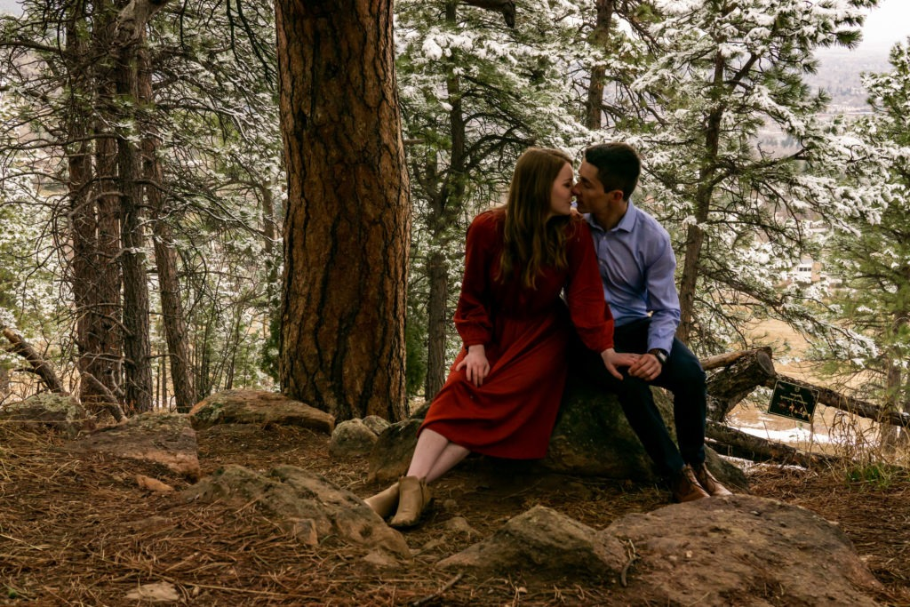 A couple sitting on a rock about to kiss in a snowy forest during this Boulder engagement session by Gabby Jockers Photography. boulder engagement photography, boulder engagement photos, boulder engagement session, chautauqua park engagement photos, chautauqua park engagement session, chautauqua park photography, Flatirons engagement photos, snowy engagement photos, snowy engagement session, hiking engagement, adventure photos, adventure session, couples photos