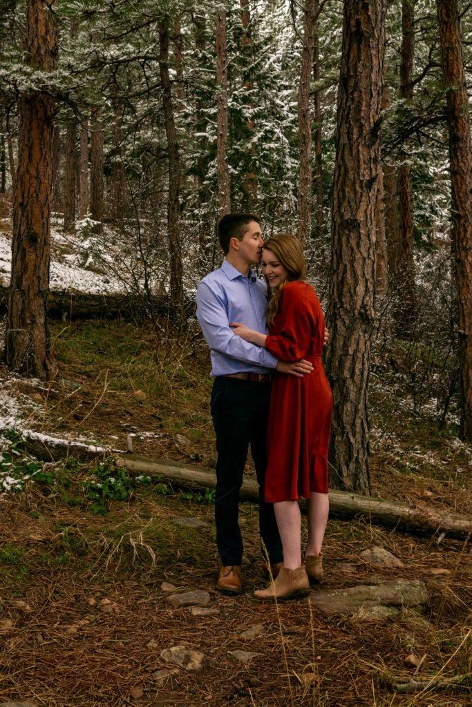 A man kissing his fiance's forehead in a snowy forest during this Boulder engagement session by Gabby Jockers Photography. boulder engagement photography, boulder engagement photos, boulder engagement session, chautauqua park engagement photos, chautauqua park engagement session, chautauqua park photography, Flatirons engagement photos, snowy engagement photos, snowy engagement session, hiking engagement, adventure photos, adventure session, couples photos